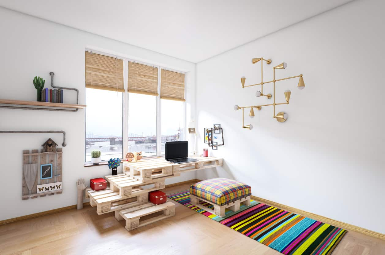 Spacious urban chic home office with white walls decorated featuring a decorative industrial copper lighting, a floating shelf with pipes, woven blinds, crates that make up a stylish desk with storage and paired with a cushioned crate ottoman, and a colorful rug on the wooden flooring.