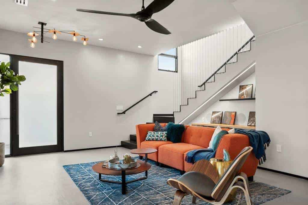 Charming living room with orange sectional sofa paired with blue throw pillows and throw blanket over a blue abstract rug. It has a ceiling fan and an eye-catcher industrial pendant lighting fixture.