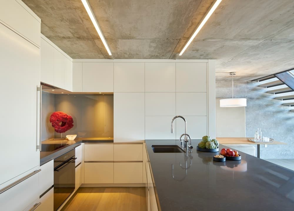 Elegant and tech-savvy best describe this modern kitchen design. Although the furnishings are totally plain, the combination of pale and dark tones makes this place look brilliant nonetheless. A few bright and colorful decorations add life to the kitchen while the sleek ceiling lights illuminate the whole place.