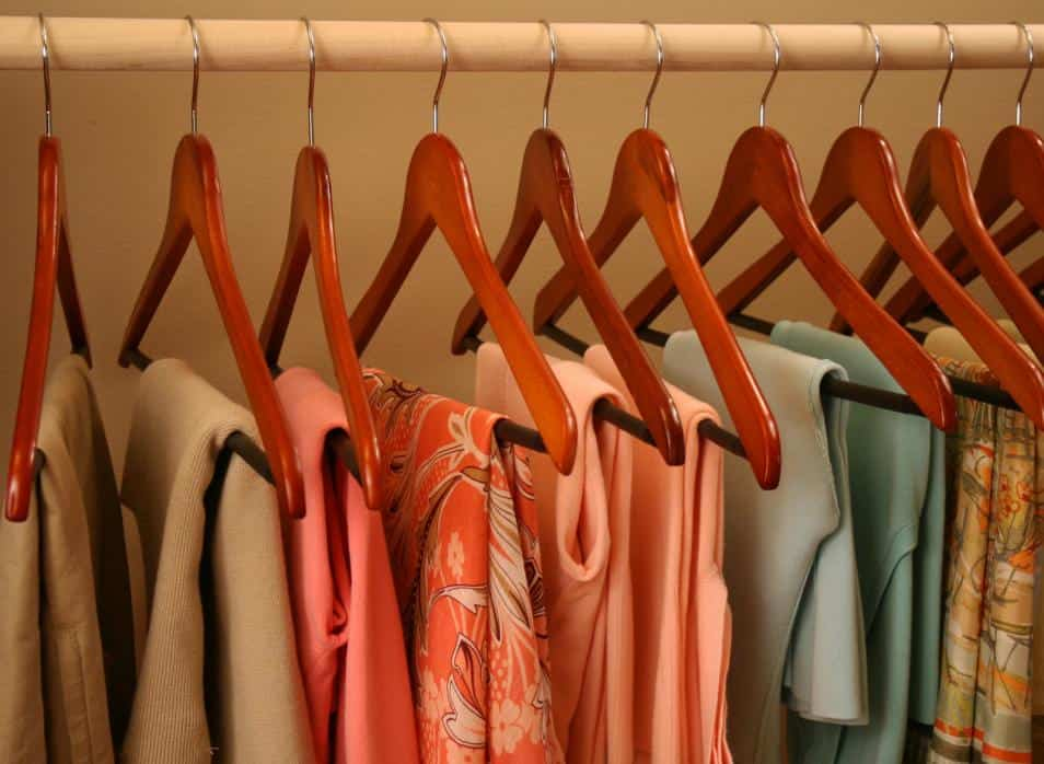 Colorful sweaters hanging in a closet
