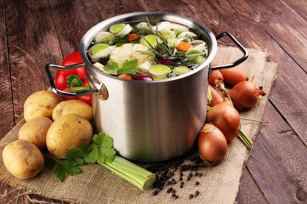 Stock pot filled to the brim surrounded by potatoes and onions.