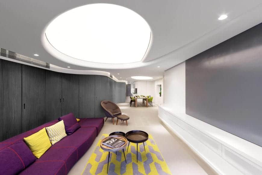 The circular concave ceiling with recessed lighting is making a statement on this stylish modern living room. A long purple sofa with a pop of yellow back pillows and printed rug contrasts the neutral color of the wall, cabinets and floor.