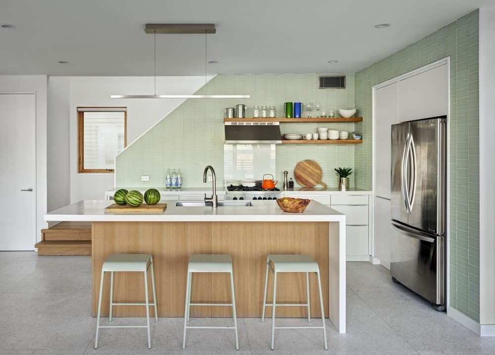 This totally chic kitchen seems to be a modern studio art. It's kept simple yet artistic by displaying different crockery on open shelves while the soft and subtle pastel green color is miles away from the conventional colors used in most kitchens.