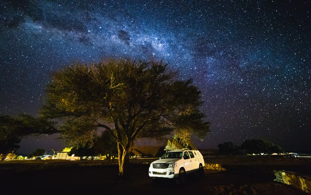 An SUV parked near a tree under breathtaking clear night sky views.