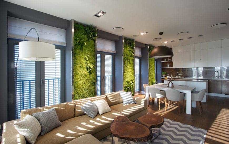 An eye-catching vertical green wall with real living plants accentuate this Eco-friendly living room. It includes an L-shaped beige sectional sofa paired with elegant tree stump coffee table over a zigzag patterned rug.