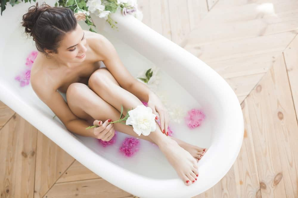 A woman taking a bath with flowers and milk.