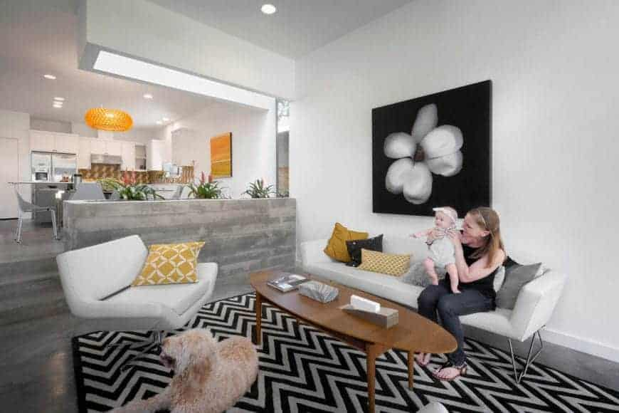 Covered with a striking zigzag patterned rug where white sofa set and wooden oval coffee sit, the living room provides a clean, fresh look. It features a concrete planter box which divides the living room from the dining room and a white flower on a black canvass that adds sophistication on the area.