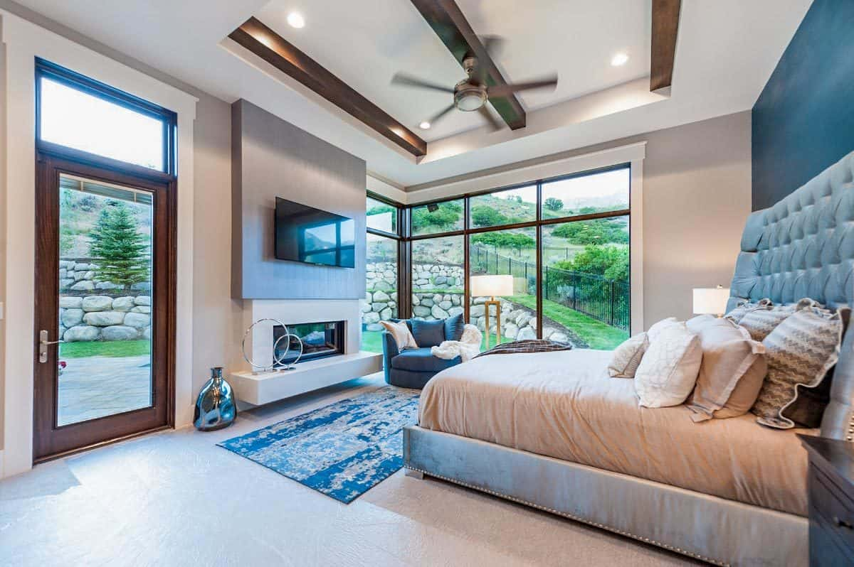 This primary bedroom features a comfy tufted bed and a sleek fireplace complemented with a cuddle chair. Its corner windows and glazed door provide an incredible view of the serene surrounding.