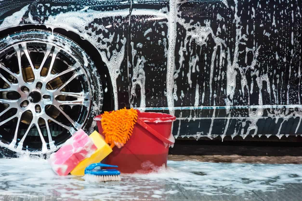Different types of car wash tools and a wet soapy black car behind.