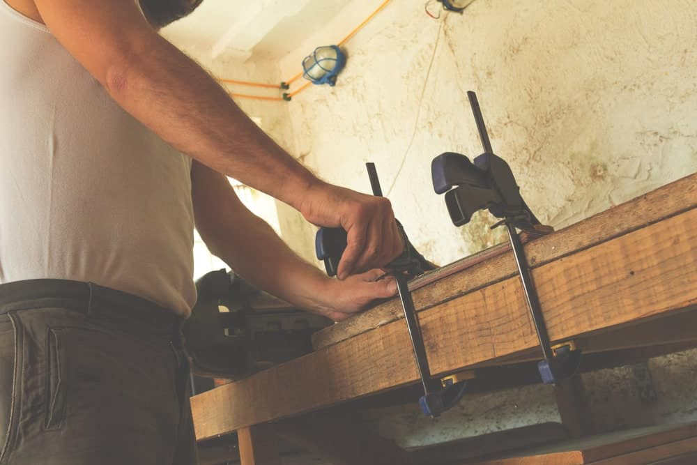 A workman using clamps for woodworking.