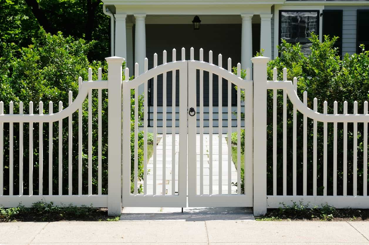 White picket fence and front gate of a home.