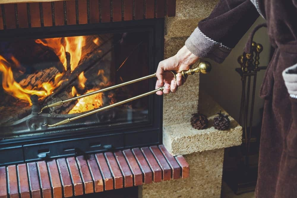 A person using fireplace tongs for moving burning fire logs.