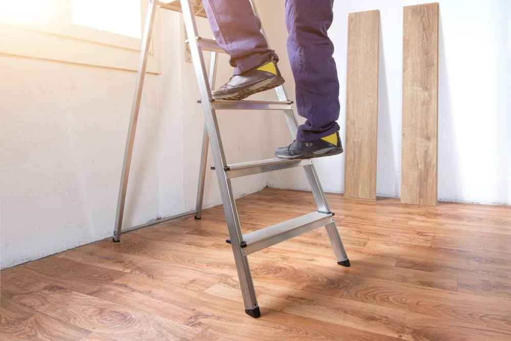 Cropped shot of a person's feet climbing up or down a ladder inside a room with wooden flooring.