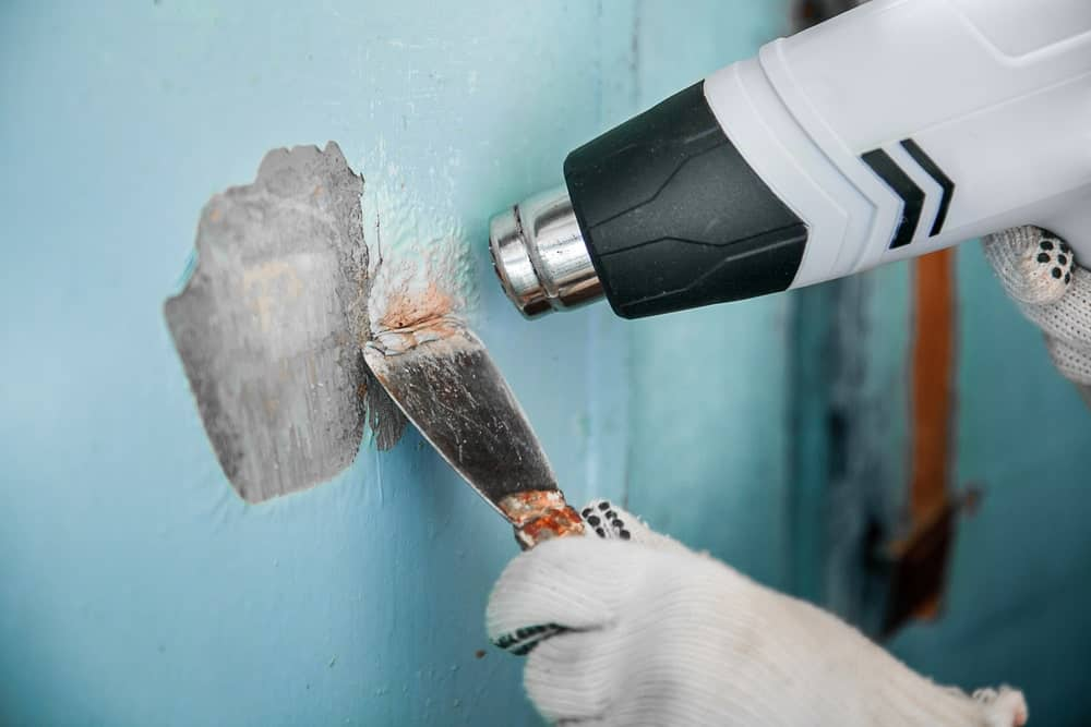Removing old paint from the walls using paint removal tools.