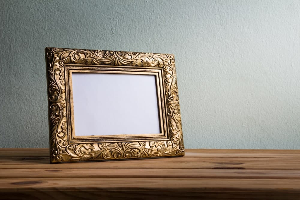 An empty decorative picture frame on a wooden desk.