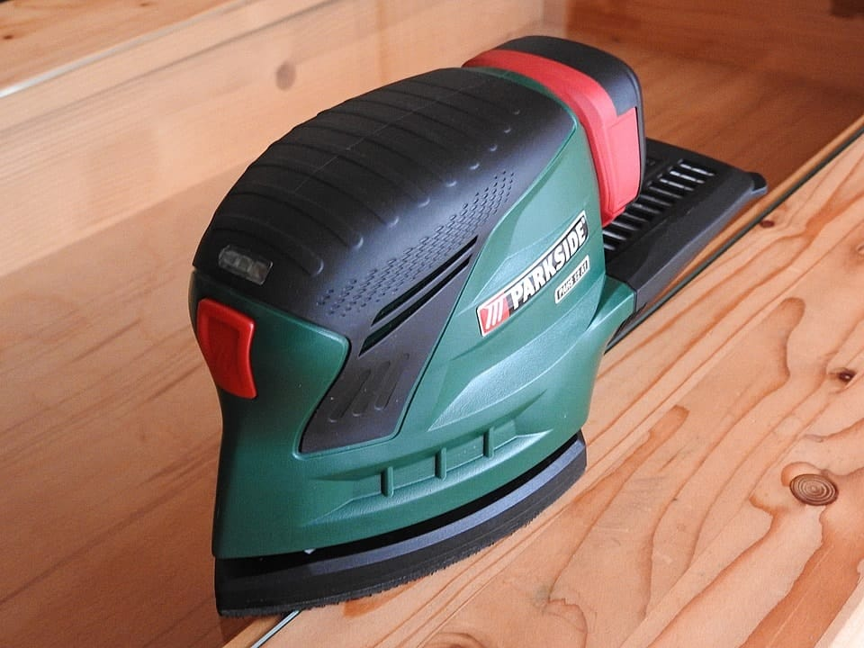 A sander on a wooden surface.