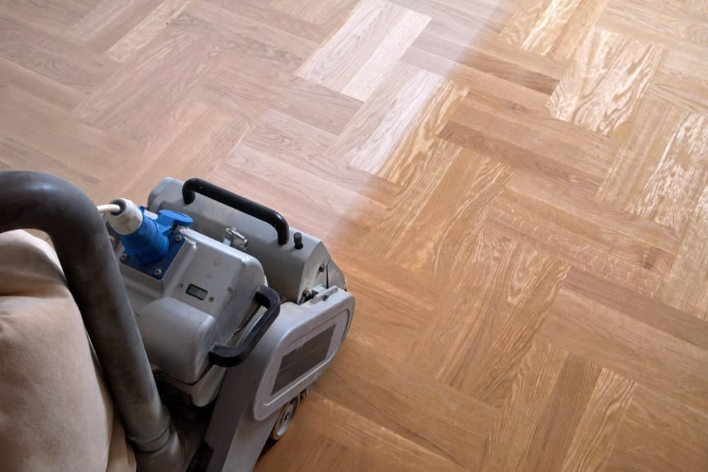 Sanding a wooden flooring using a sanding tool.