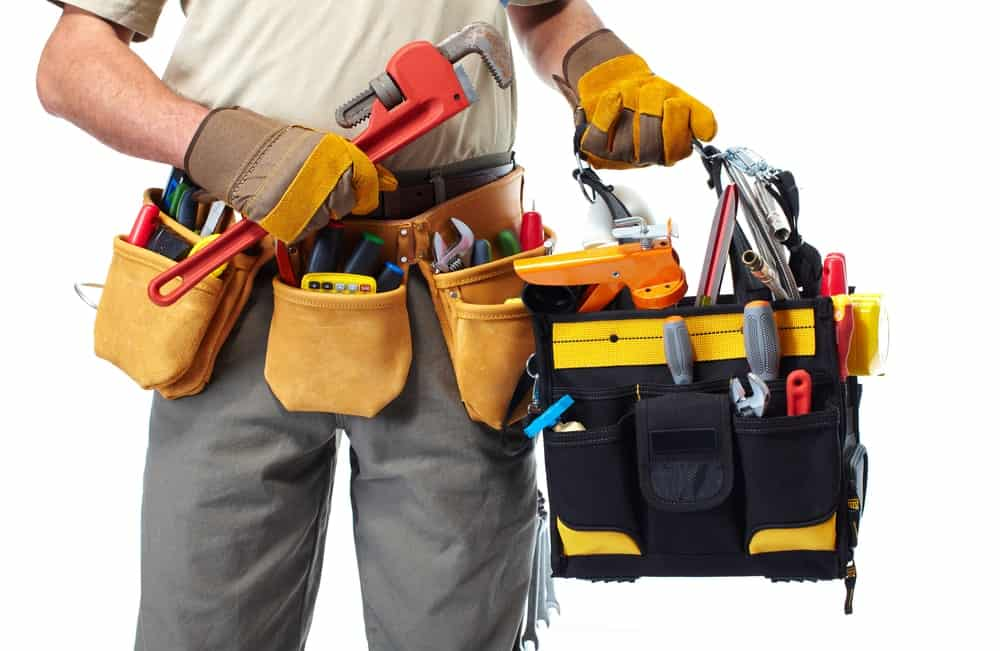 A worker wearing a tool belt and holding a bag full of tools.