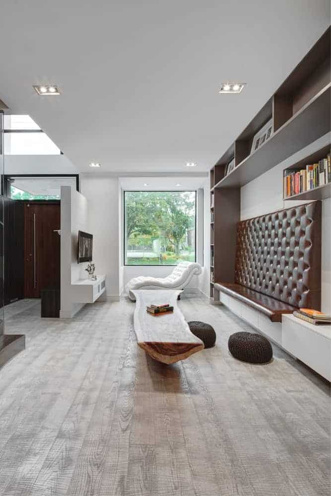 Built-in shelves and a leather tufted high back sofa paired with a trunk tree coffee table and twin round knitted ottomans over a light colored hardwood flooring. A modern white chaise lounge contrasts with wood and brown furniture. Beside it is a picture window that helps brighten the space.