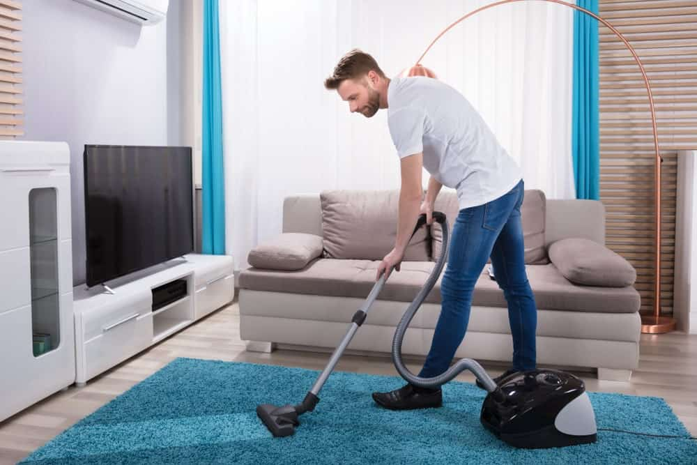 Man using a vacuum cleaner on the living room rug.
