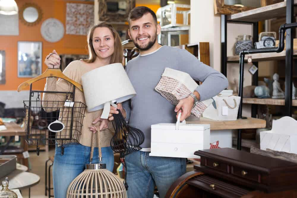 Couple showing off their finds of vintage home decorating items.