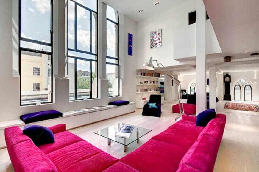 An airy living room with its high ceiling and tall glass windows. It features a V-shaped pink velvet sofa with dark violet throw pillows which makes the room appear livelier.