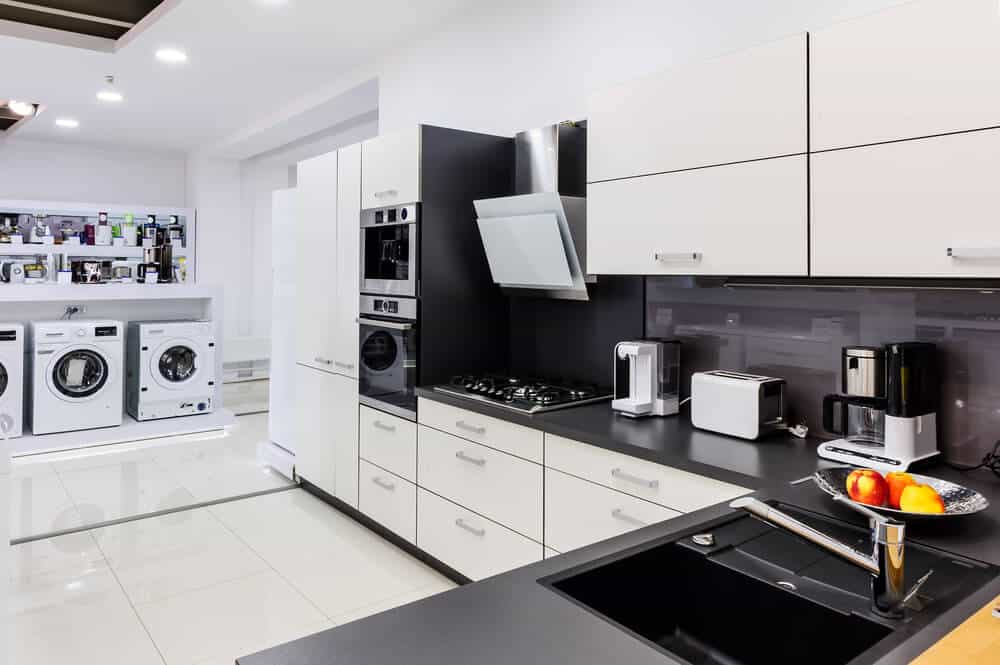 Shop display of white appliances and a white kitchen showroom with modern appliances.