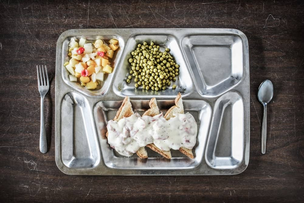 Top view of a food served in a serving tray with compartments with the spoon and fork on both sides of the tray.