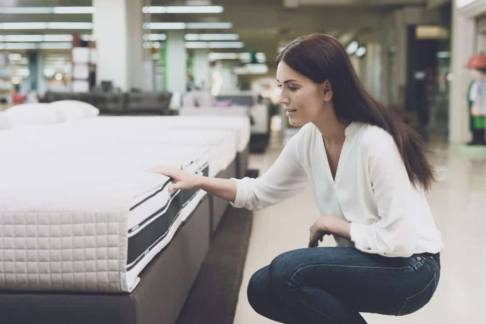 A woman checking a mattress at a store.