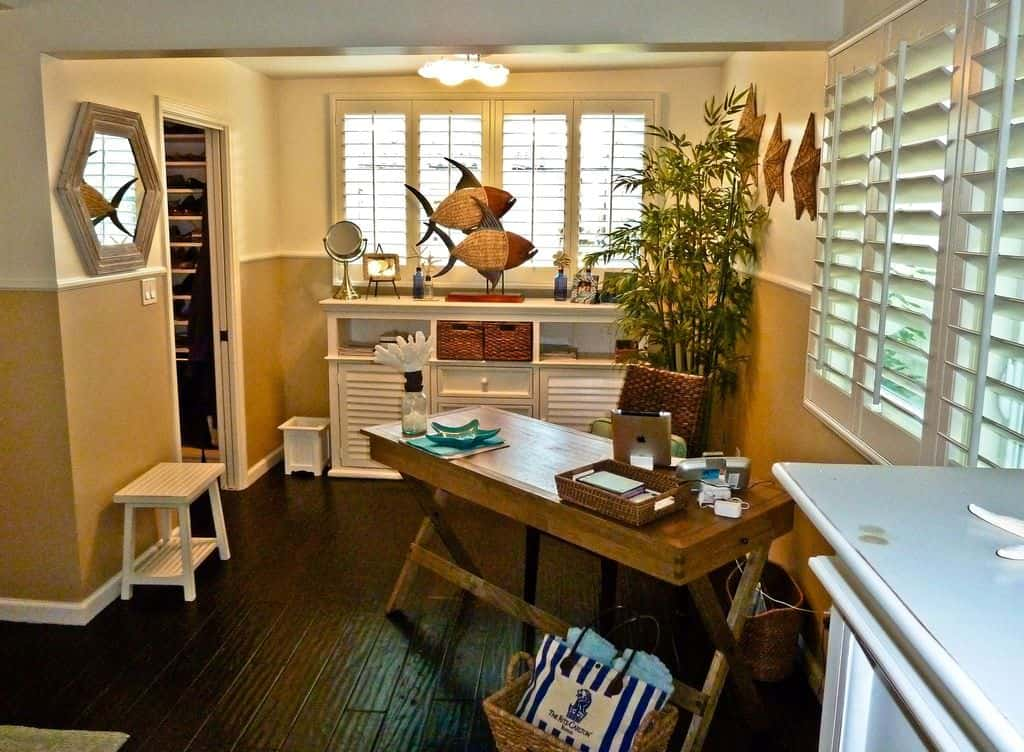 Tropical style home office with shutter windows, woven furniture and accessories such as the wall stars and hanging fishes, an indoor plant, rustic table, and wood flooring.