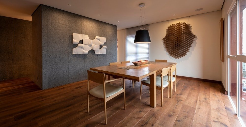This is the dining room of the apartment with a wooden dining table that matches with the hardwood flooring and the wall-mounted sculpture of a tribal mask on the far wall.
