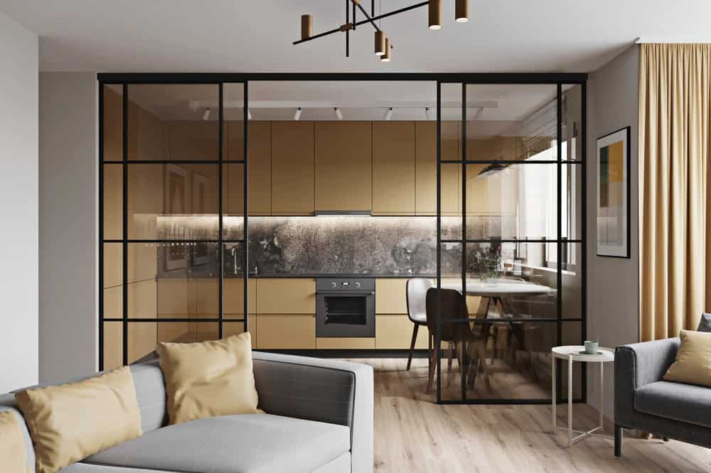 This is a close look at the apartment living room with a set of gray sofa and has a clear view of the kitchen and dining area through a set of glass walls that slide to open.