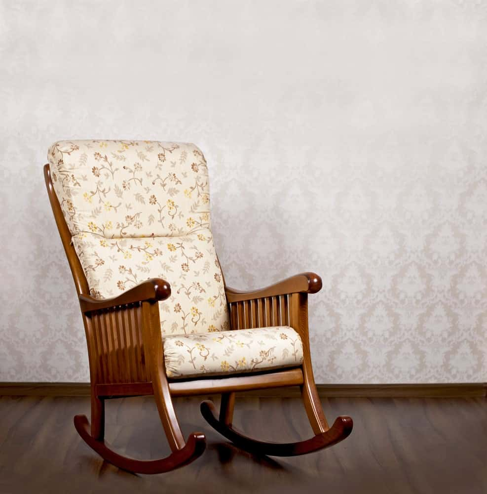 A modern wooden rocking chair with white covers with a white wall in the background