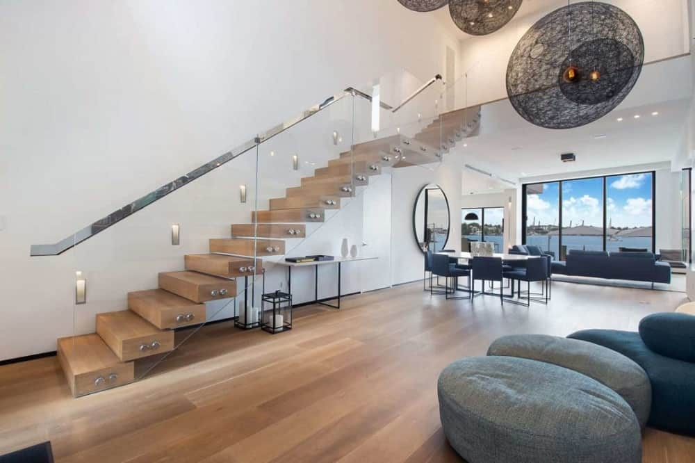 Upon entry into the house, you are welcomed by this spacious and bright foyer with glass walls on the stairs and multiple decorative lighting hanging from the tall ceiling.