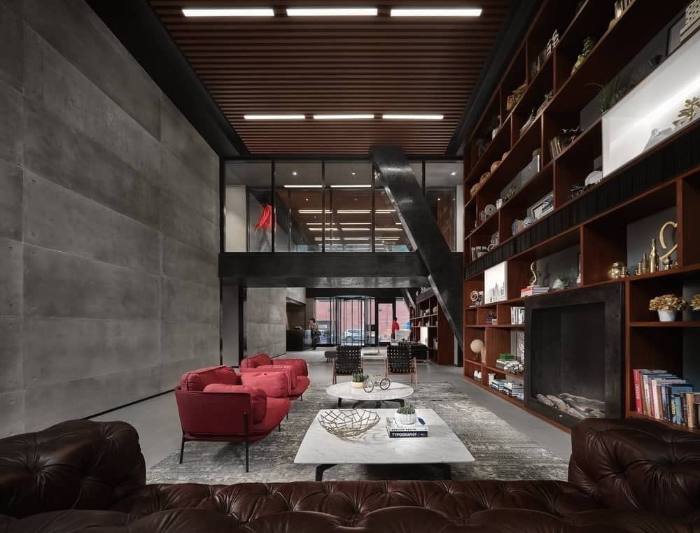 This is a spacious living room with a tall ceiling, gray walls and gray frlooring that makes the red cushioned armchairs stand out. This is paired with white coffee tables and a large built-in wooden structure that houses shelves and the fireplace.