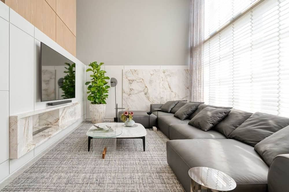 This is a full view of the apartment's living room with a large gray leather sectional sofa across from the wall-mounted TV, modern fireplace and potted plant. These are all complemented by the large glass wall behind the sofa. This was designed by STUDIOCOLNAGHI ARQUITETURA.