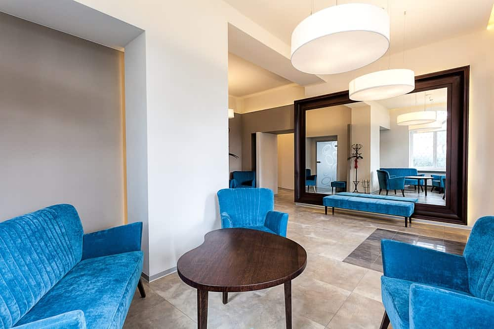 Blue sofa and armchairs set in a foyer with a contemporary wooden table in the center