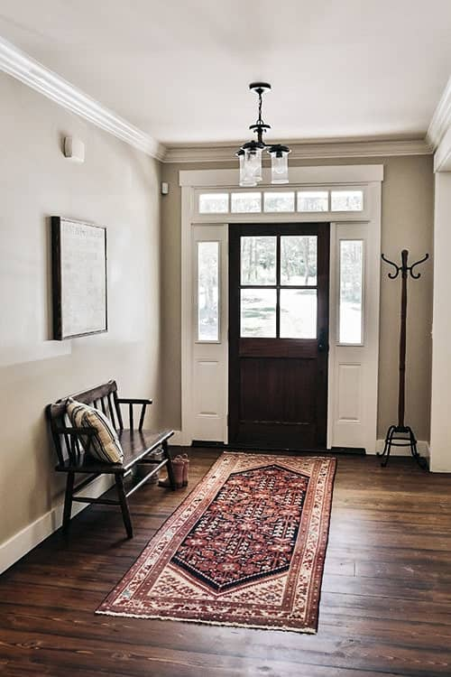 This charming foyer has an extra welcome to its guests with a dark wooden bench on the side. This matches quite well with the dark wooden main door with glass panels and the hardwood flooring topped with a colorful patterned area rug.