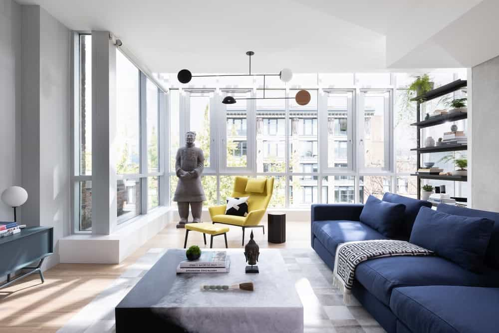This is the bright and airy living room with a large navy blue sectional sofa and a life-size stone statue at the corner.