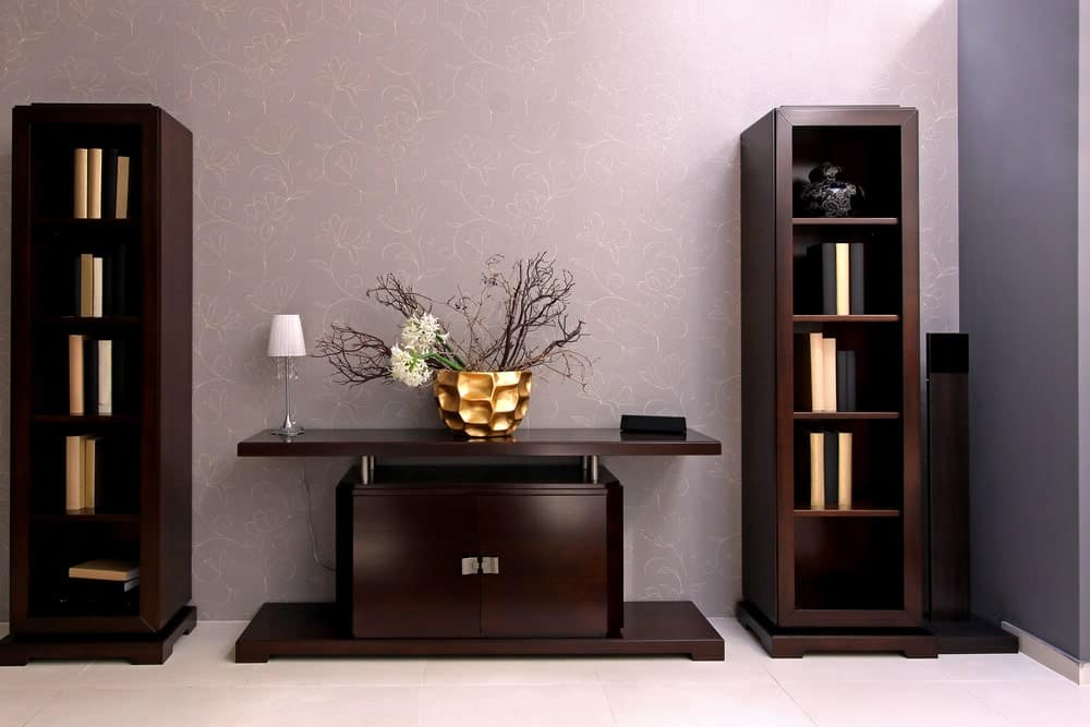 A foyer area sporting a wooden table with contemporary wooden bookshelves on both sides