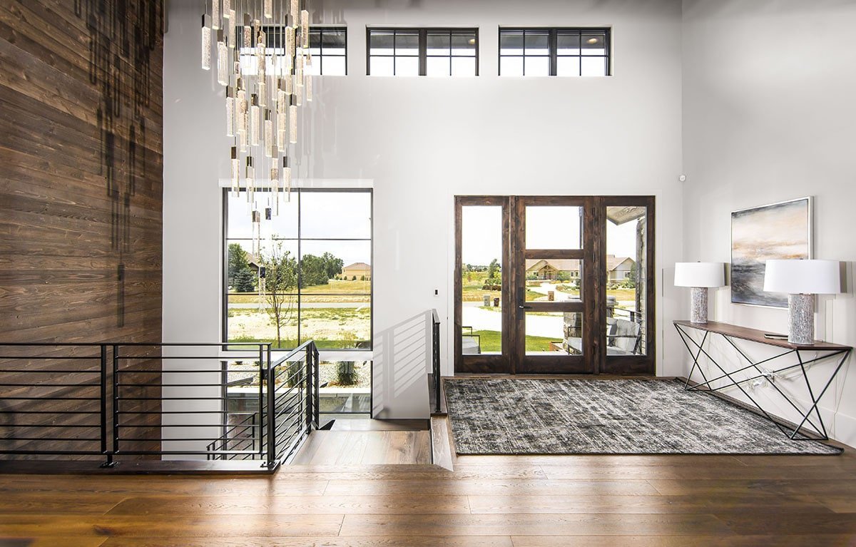 A modern foyer with rustic touches showcasing its large distressed rug and a glazed entry door flanked by sidelights.