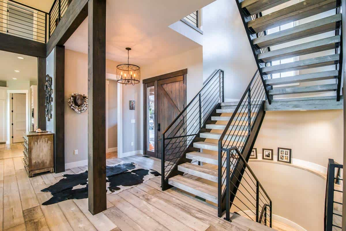 This is a simple yet gorgeous foyer with a large wooden main door adorned with a glass side light to bring in natural lighting. The light hardwood flooring of the foyer is topped with a rustic animal fur area rug and topped with a warm lantern-like round lighting.