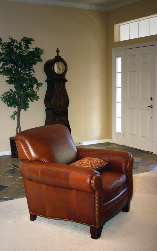 A foyer with a leather chair with armrests and a pillow in a foyer