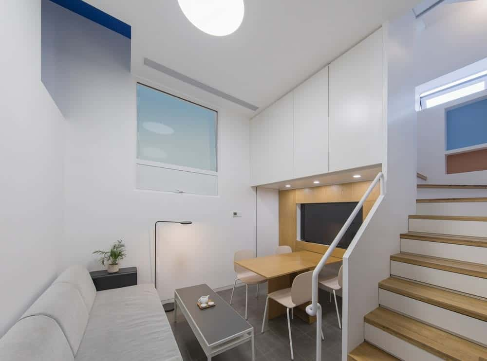 This is a compact built-in small dining area just beside the living room. It has a built-in wooden dining table attached to the wall and paired with modern white chairs that stand out against the dark flooring tiles.