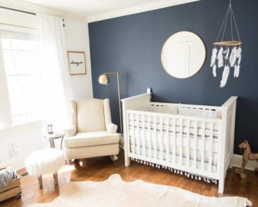 Baby boy nursery with dark blue accent wall and white crib