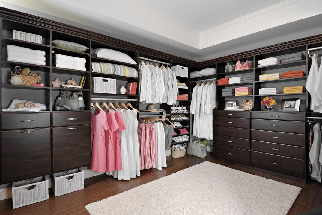 Large bedroom closet featuring a hardwood flooring topped by a white rug. The cabinetry is finished with dark brown.