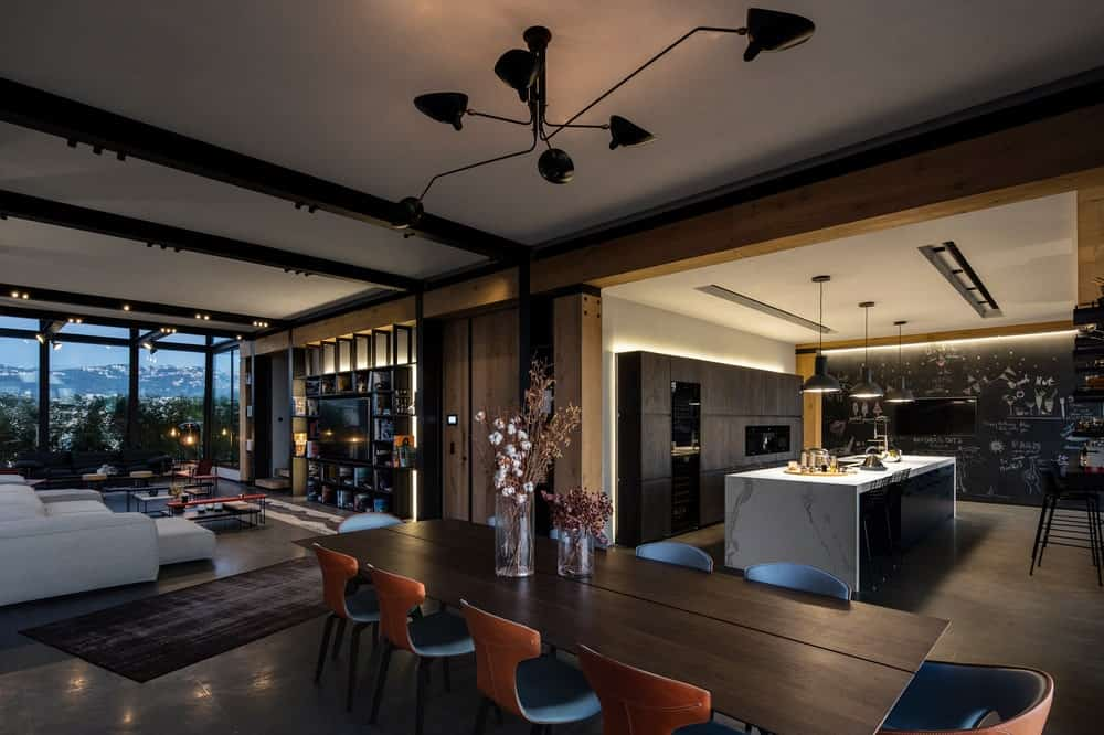 This is a view of the apartment interior showcasing the dining area, kitchen area and living room areas with open walls that connect each other. These are complemented by the black accents of the ceiling, cabinetry and the glass walls on the far side by the living room. This was designed by Atelier L'inconnu.