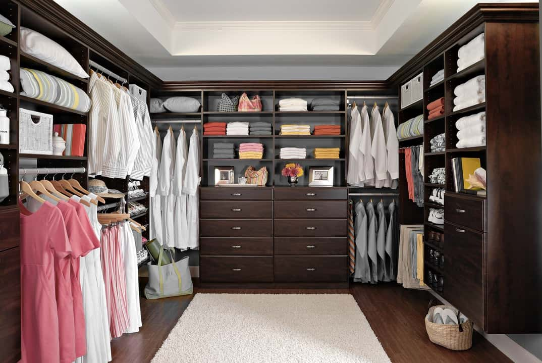 The above closet features hardwood flooring with plush rug. Custom cabinetry throughout a dark wood.