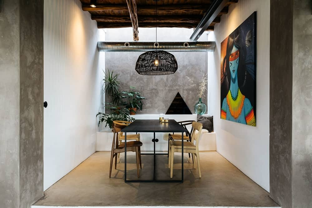 This is the dining area of the loft with a rustic charm to its wooden ceiling and woven wicker hood of the pendant light over the black dining table adorned with a large colorful painting on the side and potted plants on the far side.