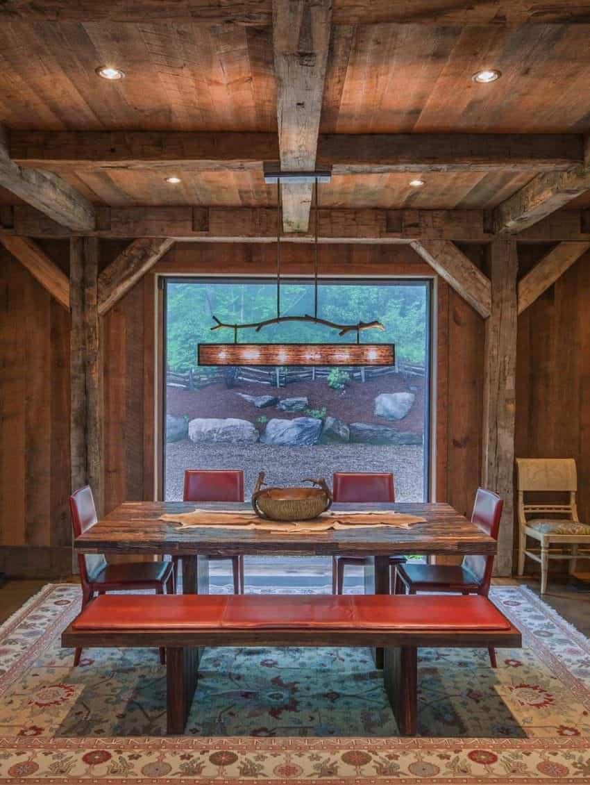 The home boasts old lumber walls and wood support beams throughout. The furniture meshes nicely with the rustic architecture. Check out that rustic dining table. The red upholstery is a nice touch color-wise.Designed by RTM Architects